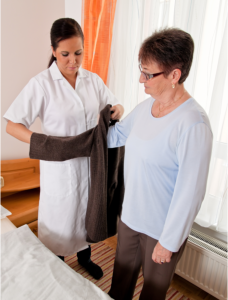 caregiver assisting her patient changing her clothes