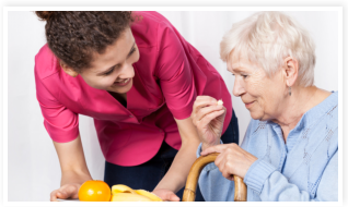 caregiver assisting her patient in taking up medicine